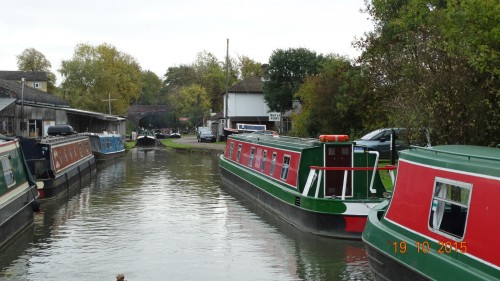 Looking back at Rose narrowboats after refilling with water. Another boat behind just coming through the swing bridge.