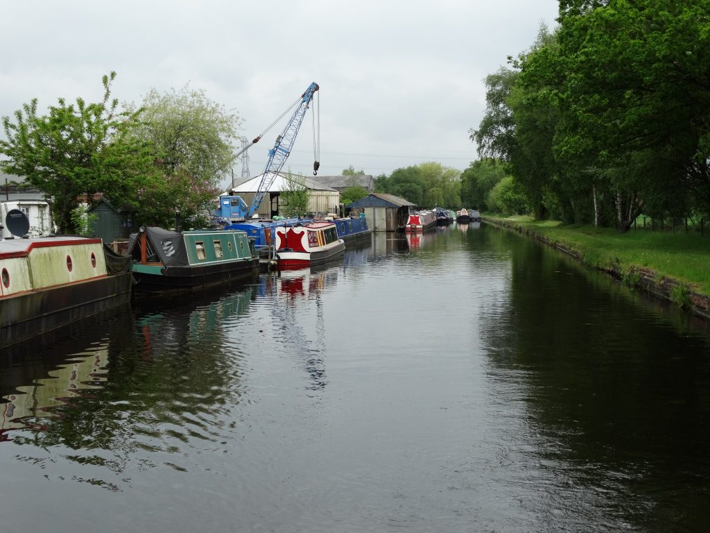 The end of the line, with moored boats along the offside. Norton Canes boatyard crane in view.